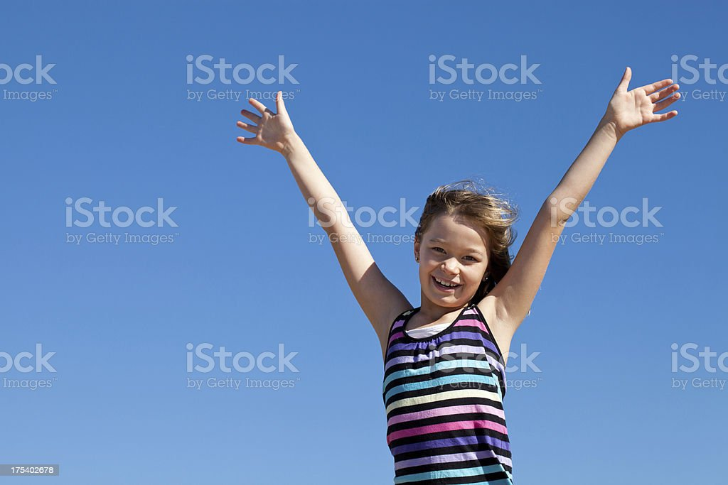 Happy little girl with arms raised up clear blue sky royalty-free stock photo