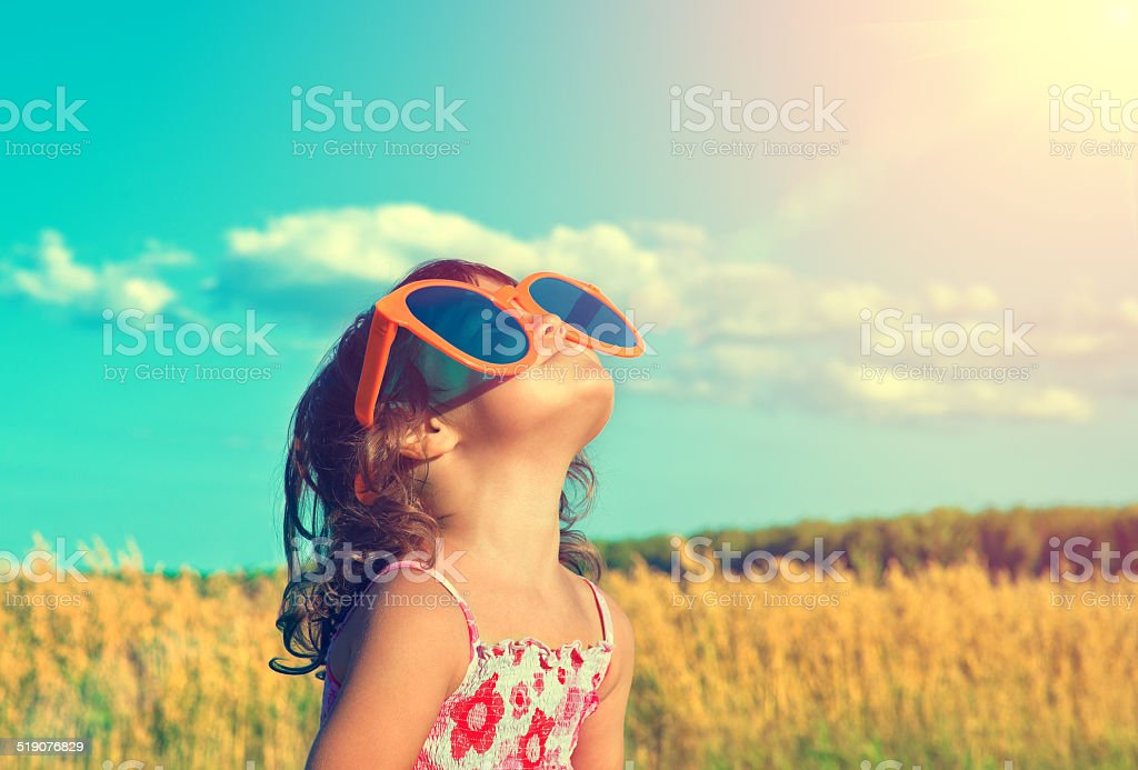 Happy little girl with big sunglasses looking at the sun stock photo