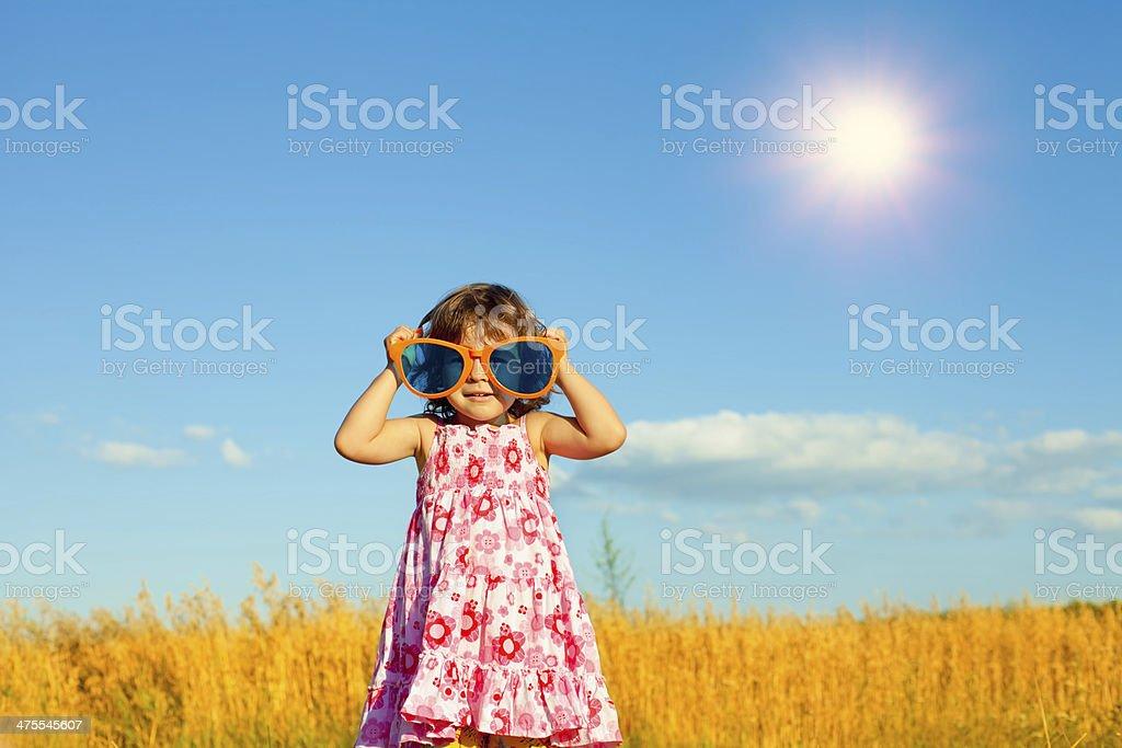 Happy little girl with big sunglasses stock photo