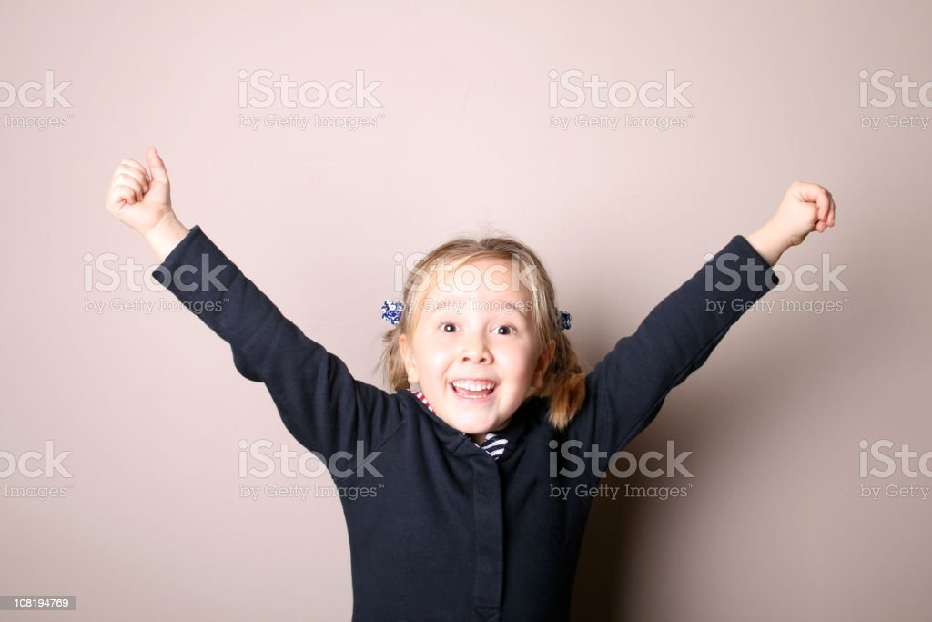 Happy little girl with her arms up royalty-free stock photo