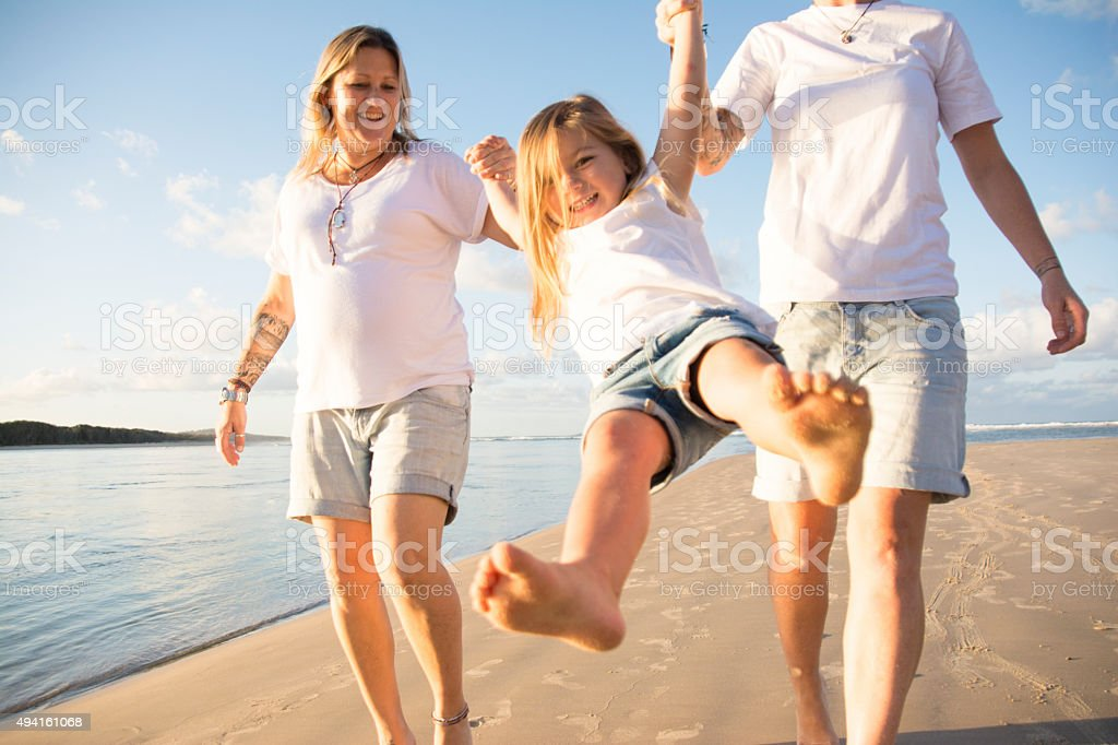 Happy little girl with her two mum's stock photo