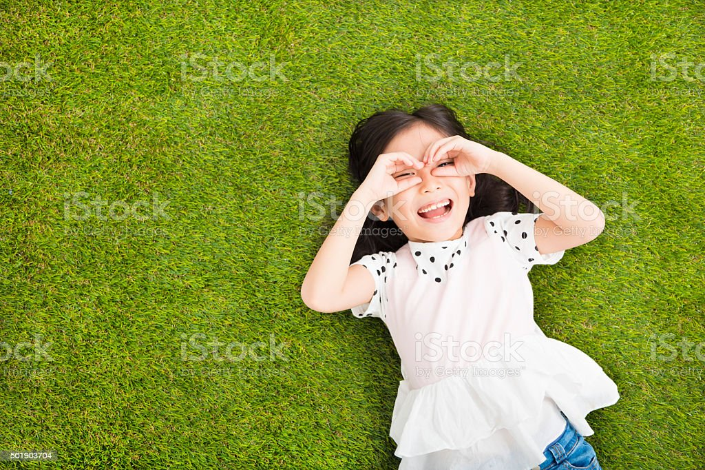 happy Little  girl with looking gesture on the grass stock photo