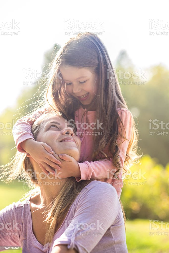 happy little girl with mom in park stock photo