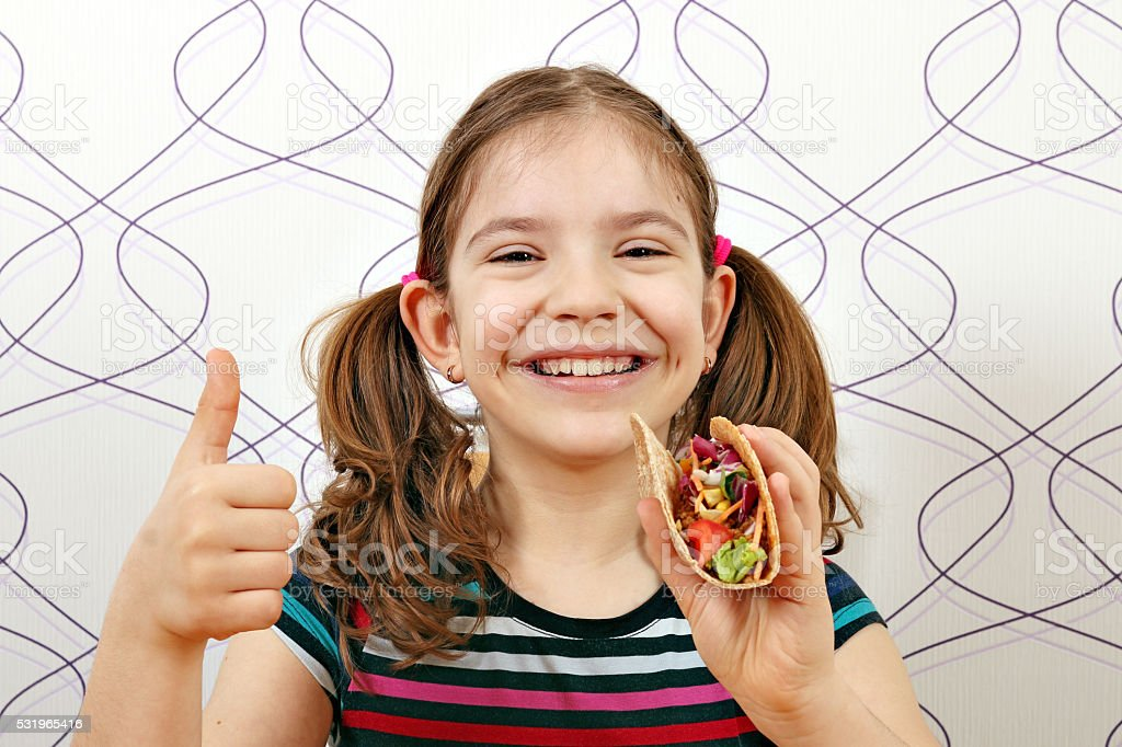happy little girl with tacos and thumb up stock photo