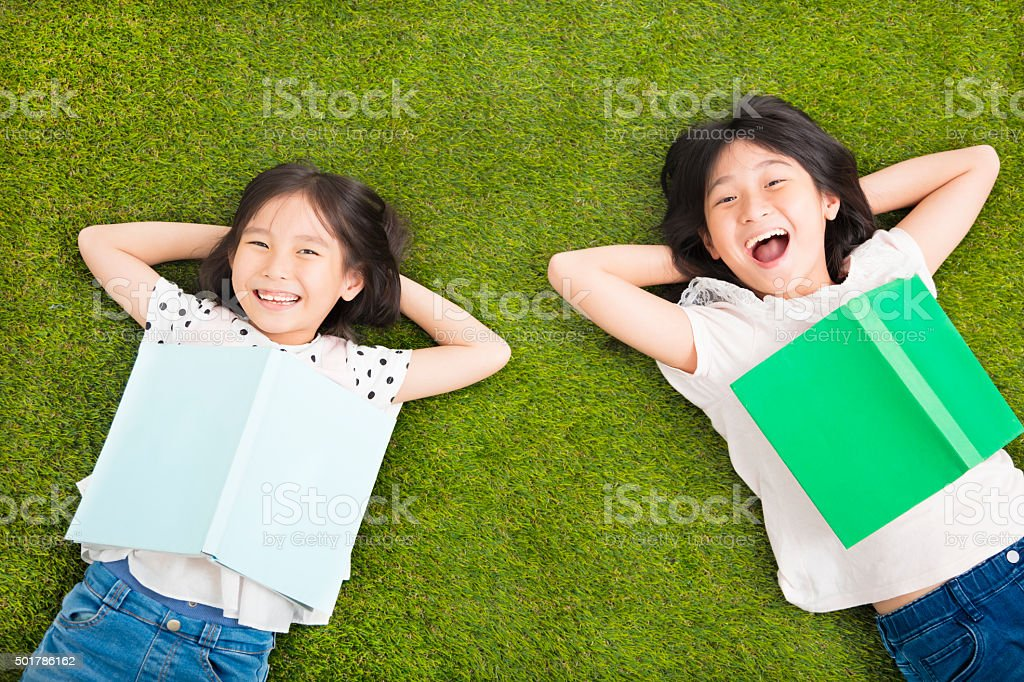 happy Little  girls with book and resting on the grass stock photo