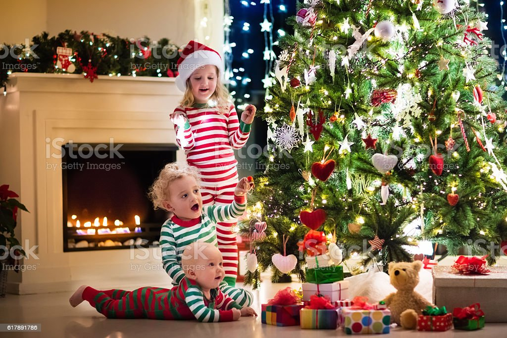 Happy little kids in pajamas under Christmas tree stock photo