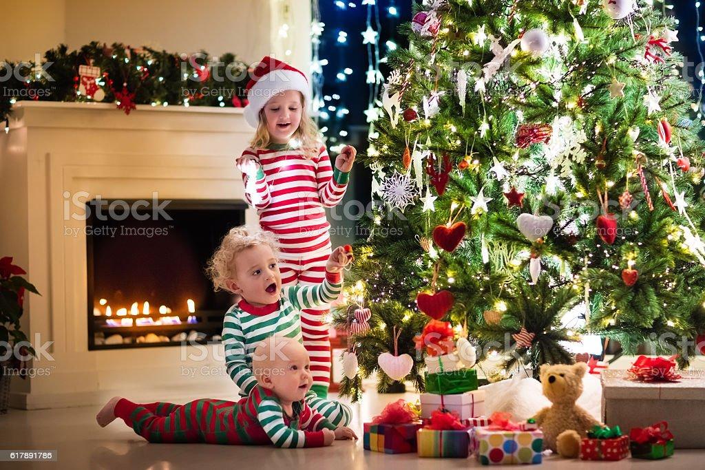 Happy little kids in pajamas under Christmas tree stock photo