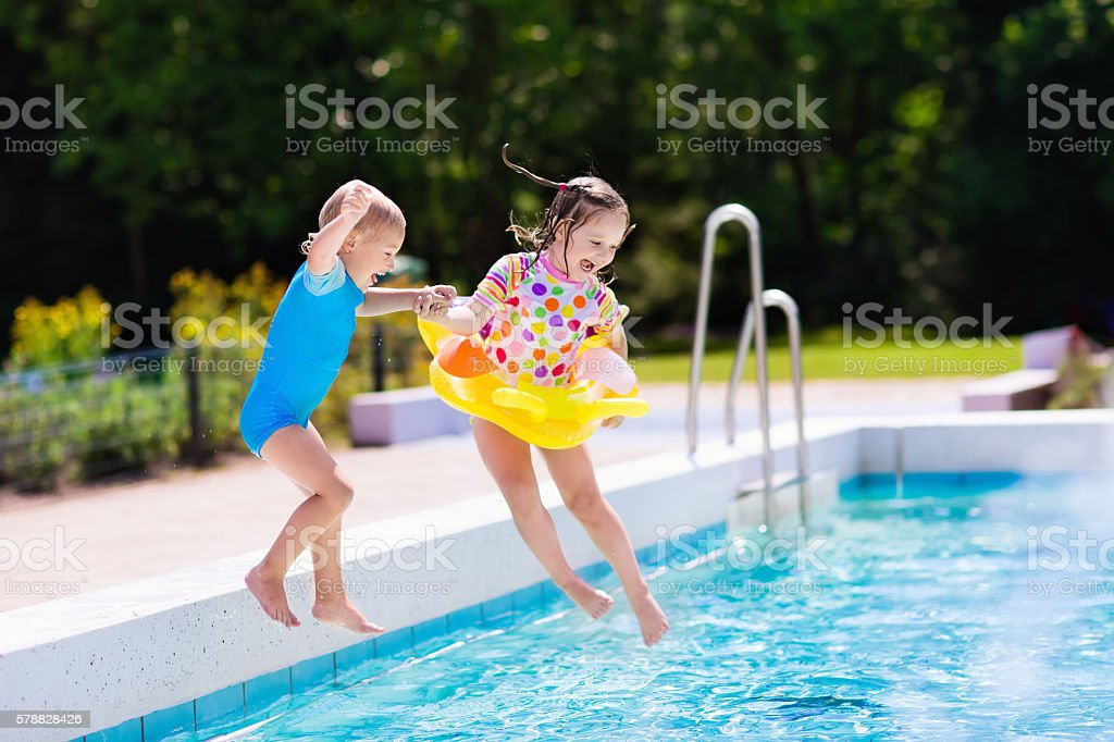 Happy little kids jumping into swimming pool stock photo