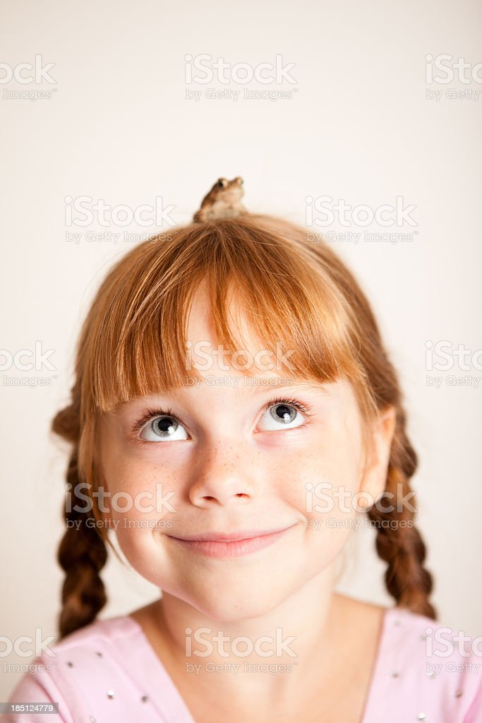 Happy Little Princess Looking Up At Frog on Her Head stock photo