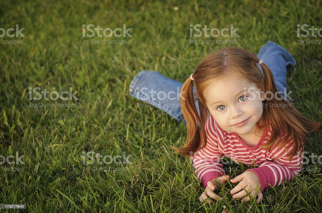 Happy Little Redhead Girl Lying in the Grass royalty-free stock photo