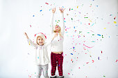 Happy little sisters enjoying confetti falling on Christmas party