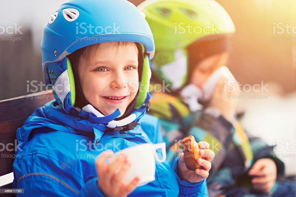 Happy little skiers resting, drinking tea and eating cookies stock photo