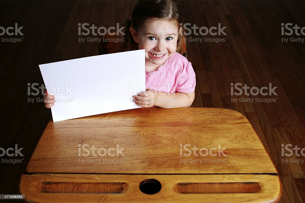 Happy Little Student in School Desk Holding Blank Sign royalty-free stock photo