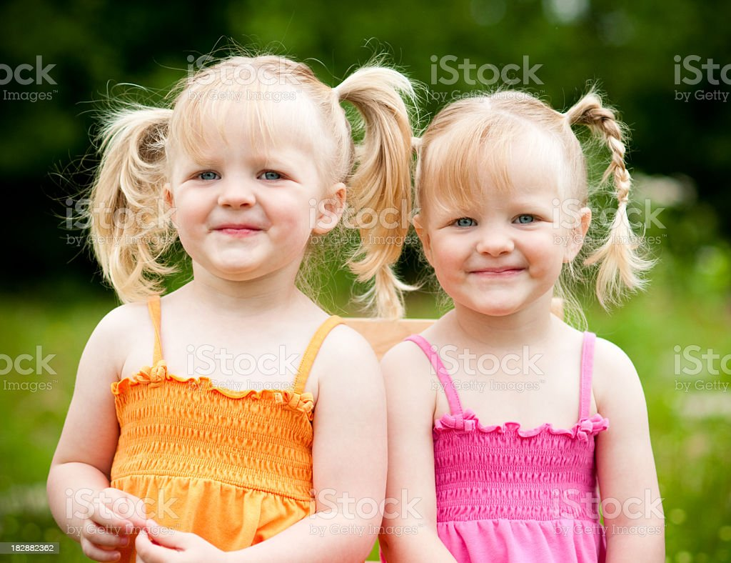 Happy Little Twin Girls Sitting and Smiling Together Outside royalty-free stock photo