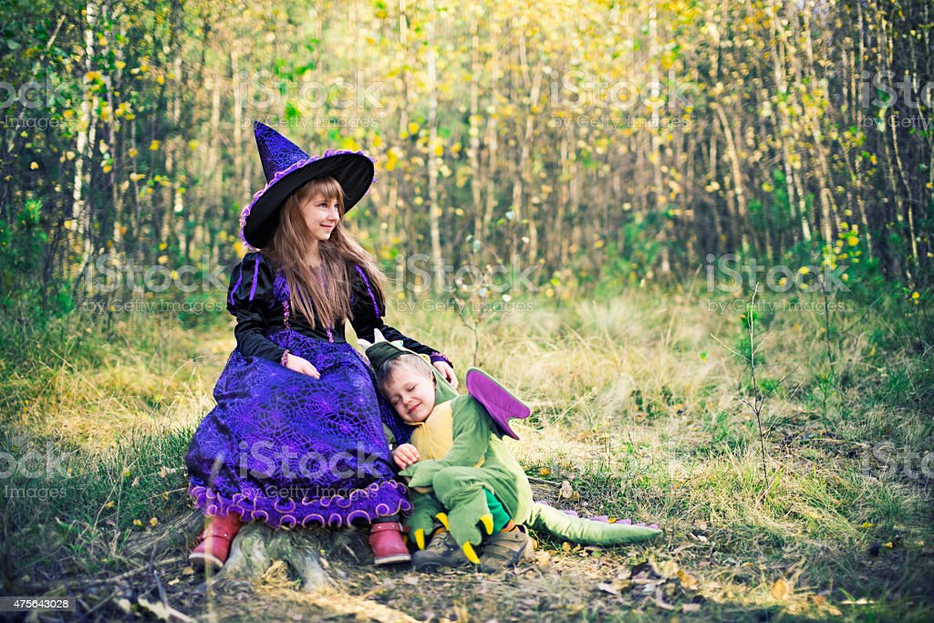 Happy little witch and pet her dragon. stock photo