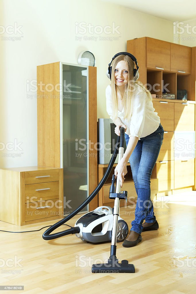 Happy long-haired woman in headphones cleaning with vacuum clean royalty-free stock photo