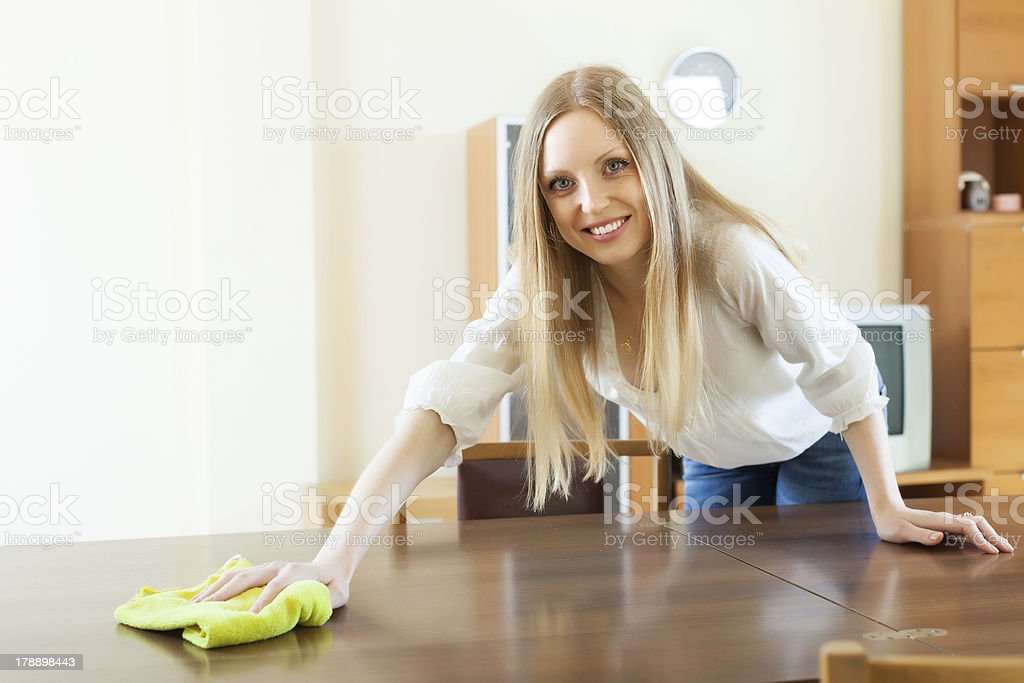 Happy  long-haired woman wiping the   table stock photo