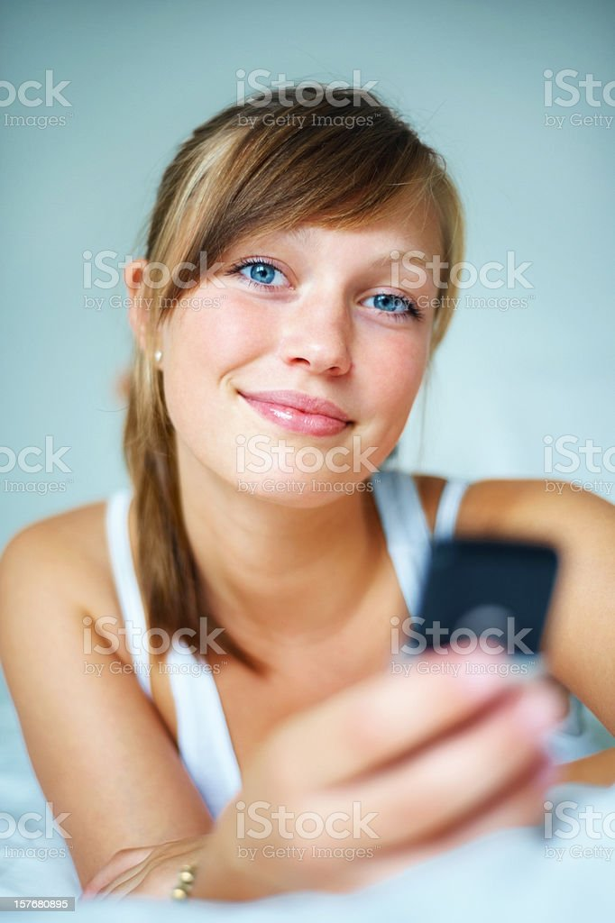 Happy looking beautiful woman with cellphone on bed royalty-free stock photo