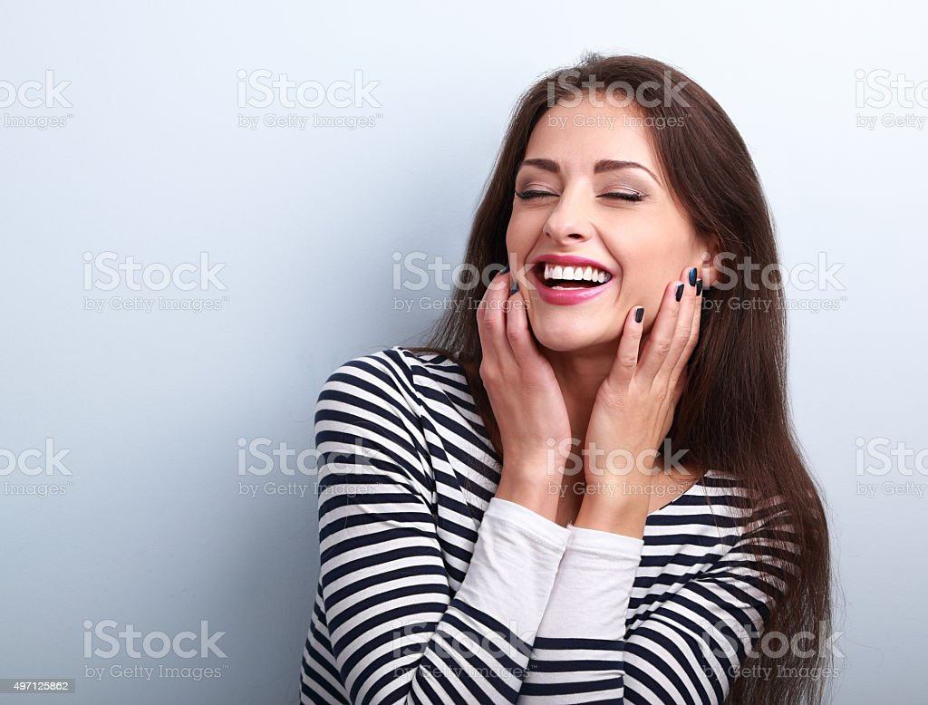 Happy loudly laughing woman holding hands the face stock photo