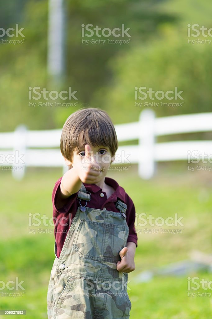 Happy lovely boy showing thumbs up stock photo