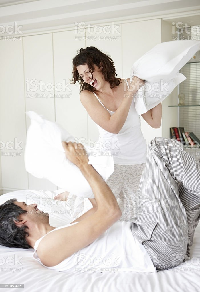 Happy loving couple having a pillow fight in bed stock photo