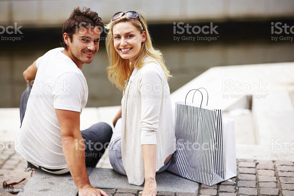 Happy, loving couple sitting with their shopping bags royalty-free stock photo