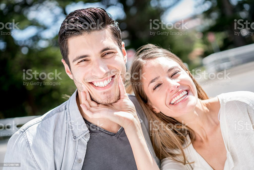 Happy loving couple smiling at the camera stock photo