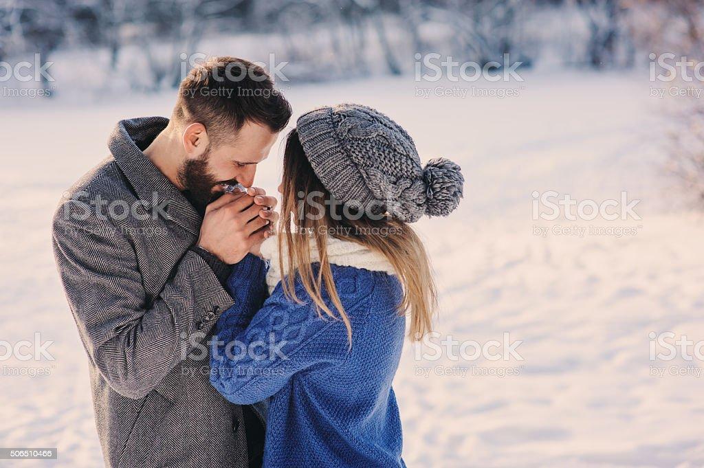happy loving couple walking in snowy winter forest stock photo