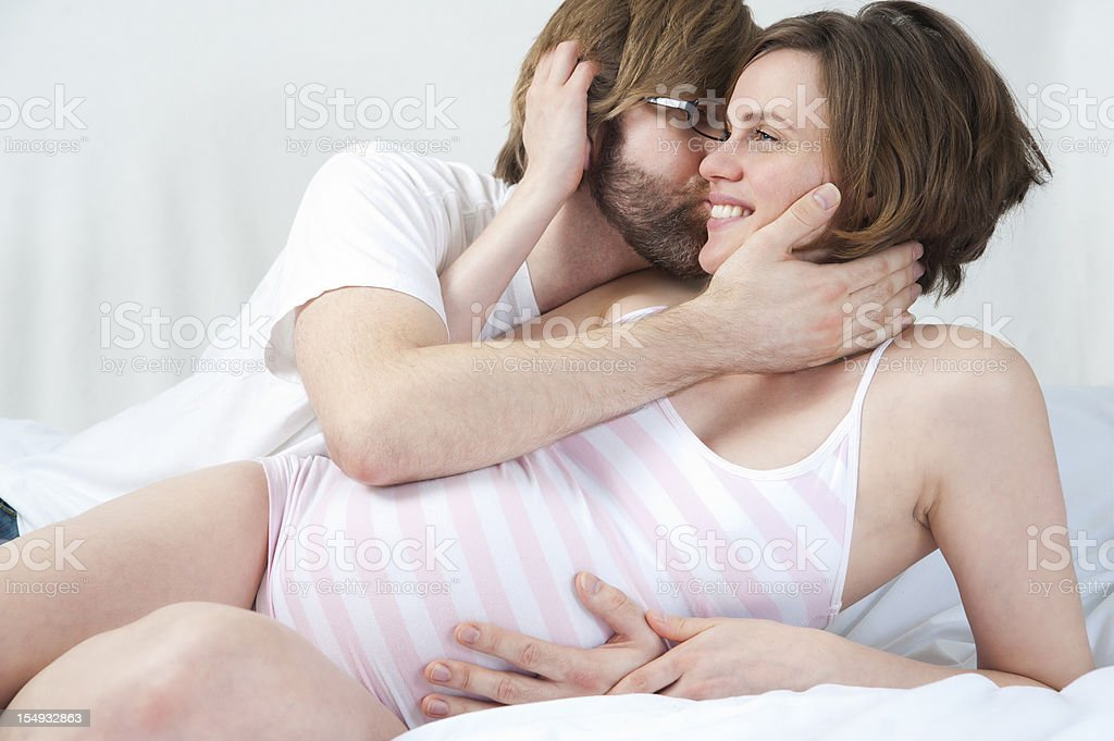 Happy loving expecting couple in embrace on bed. stock photo