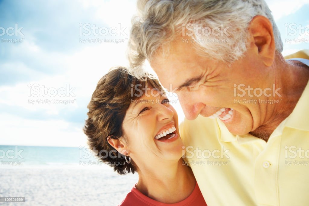 Happy loving mature man and woman laughing on beach stock photo