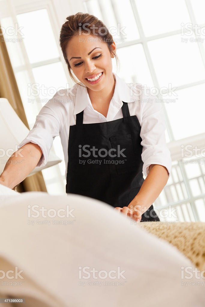Happy maid making up bed in a hotel room stock photo