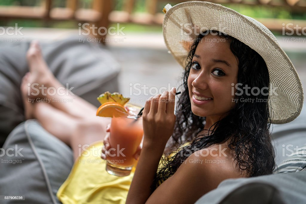 Happy Malaysian woman enjoying in a fruit cocktail outdoors. stock photo