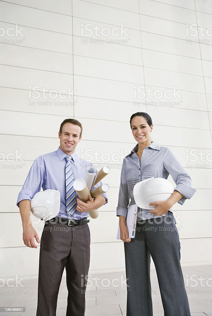 Happy male and female architects with hard hats and blue prints royalty-free stock photo