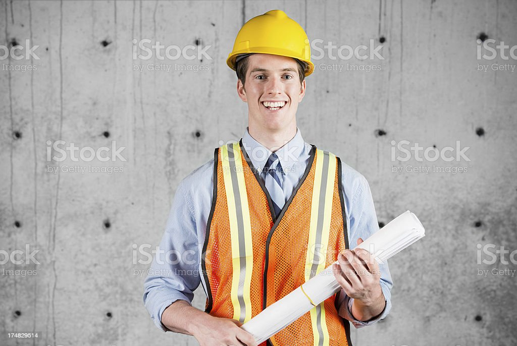 Happy male architect holding a blueprint royalty-free stock photo