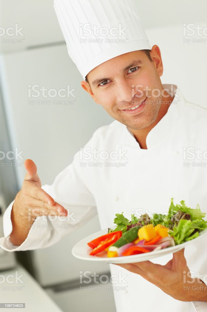 Happy male chef presenting a plate of green salad stock photo