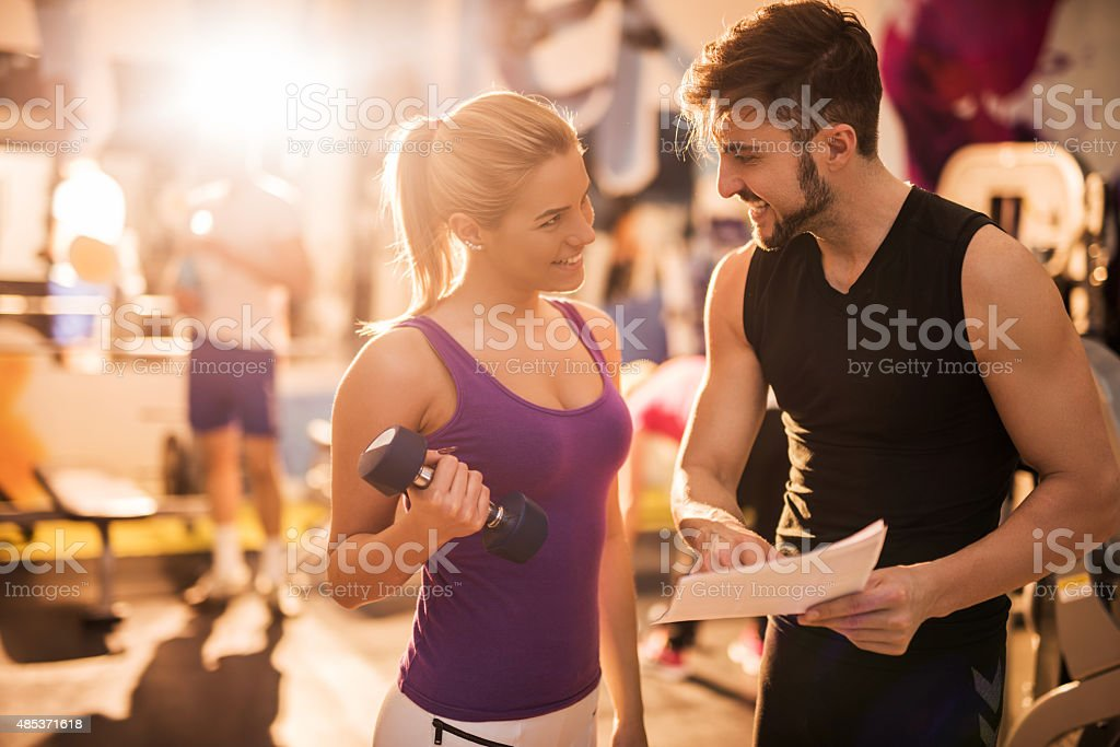 Happy male coach and young woman planning a training together. stock photo