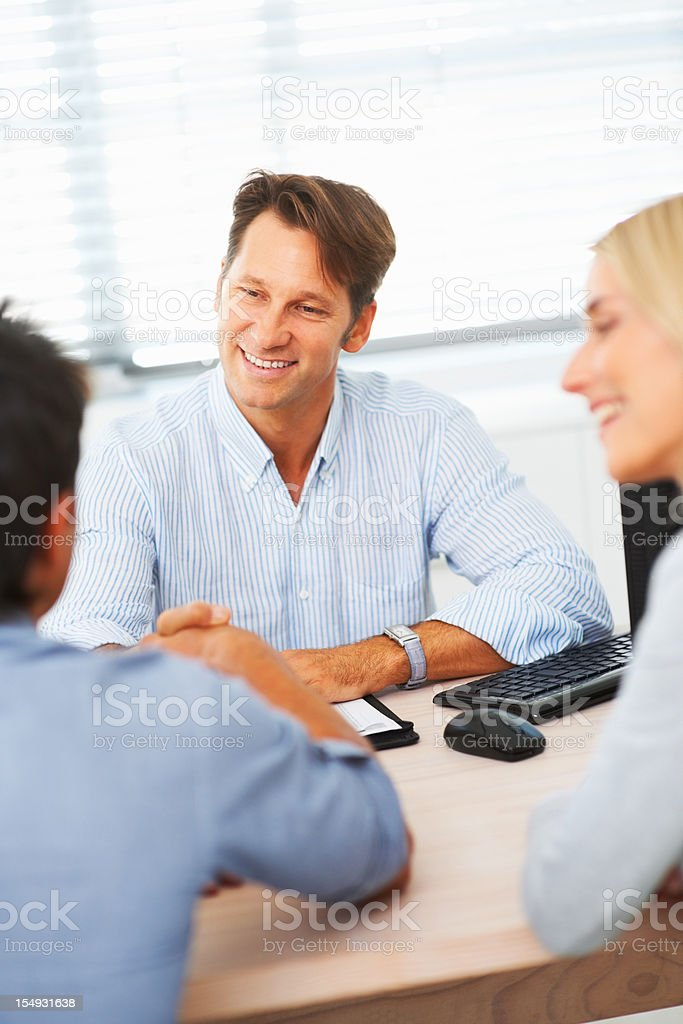 Happy male consultant greeting with clients royalty-free stock photo