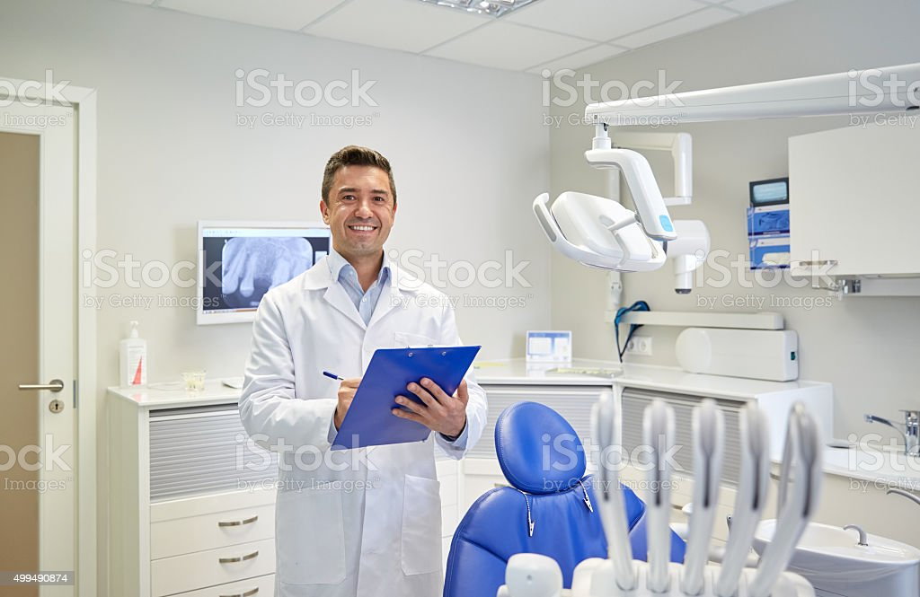 happy male dentist with clipboard at dental clinic stock photo