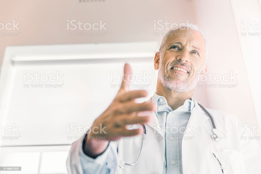 Happy male doctor offering handshake in clinic stock photo