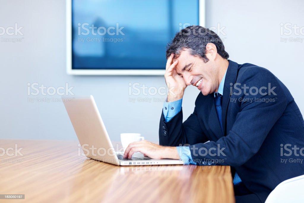 Happy male entrepreneur using laptop in boardroom royalty-free stock photo