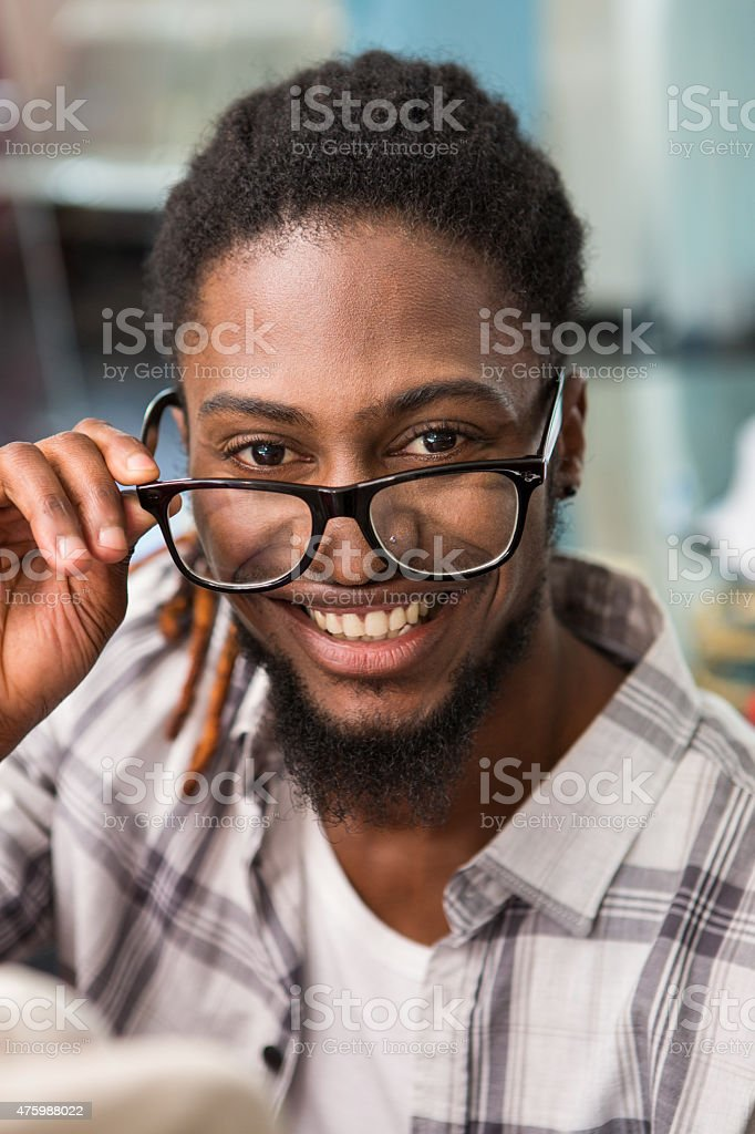 Happy male fashion designer holding eye glasses stock photo