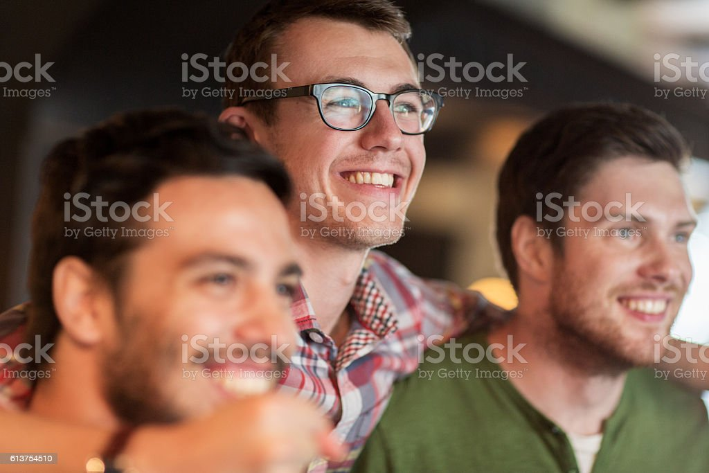 happy male friends watching football at bar or pub stock photo