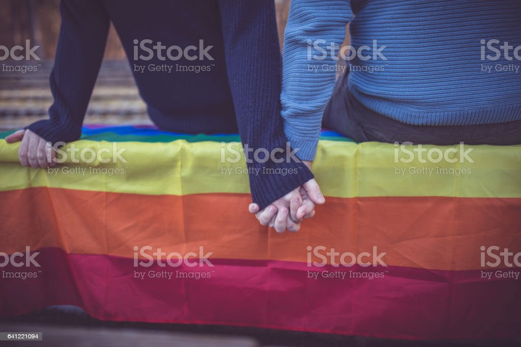 Happy male gay couple sitting on the bench in park stock photo