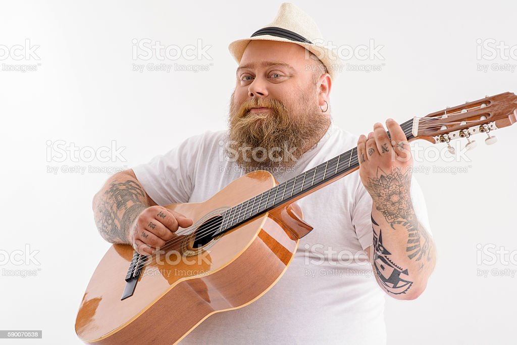 Happy male guitarist performing music stock photo