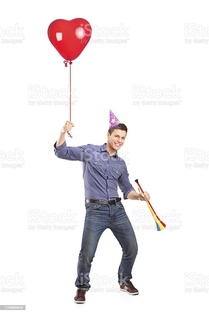 Happy male holding a balloon and horn royalty-free stock photo