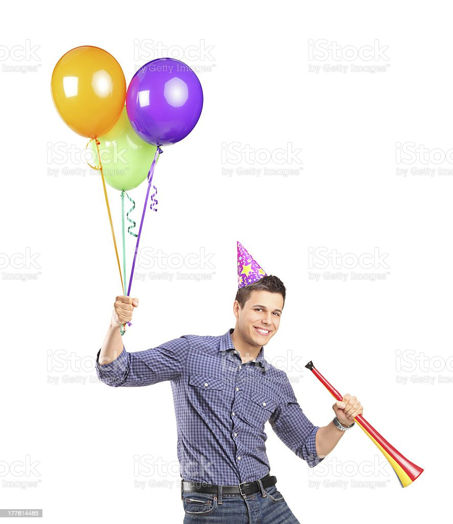 Happy male holding balloons and a horn royalty-free stock photo