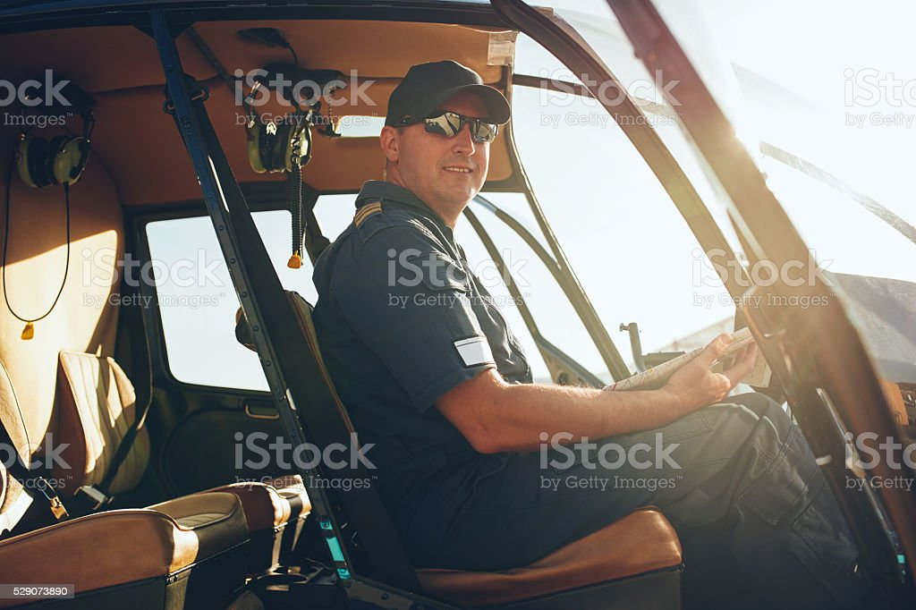 Happy male pilot in a helicopter cockpit stock photo