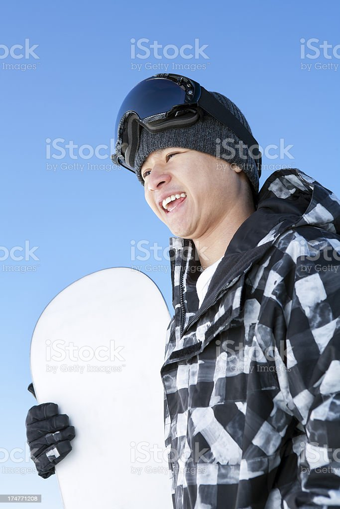 Happy male snowboarder against blue sky royalty-free stock photo