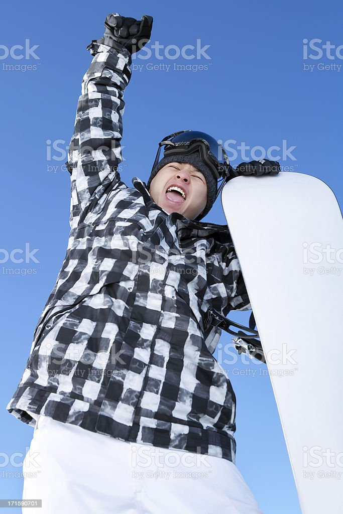Happy male snowboarder with arms raised stock photo