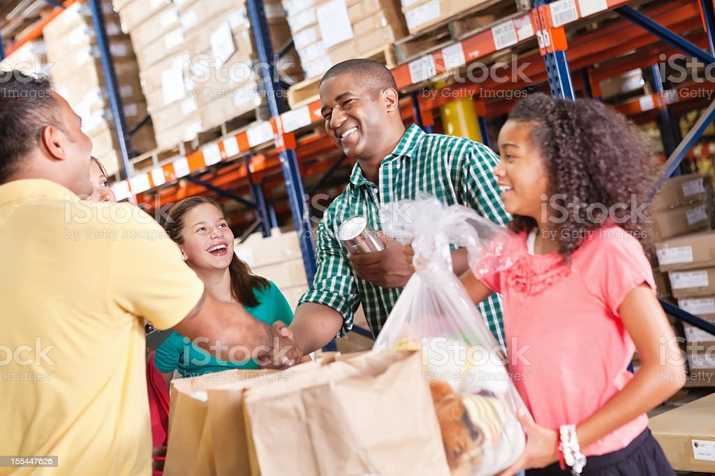 Happy man and daughter making donations at a food pantry stock photo